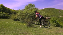 Girl mountainbiker pushing and getting on her bike Stock Footage