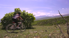 Girl mountainbiker cycling in nature on a rocky meadow Stock Footage