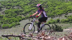 Girl mountainbiker cycling in nature on an uphill meadow Stock Footage