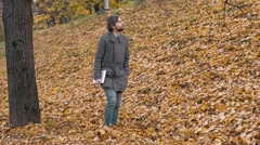Portrait of a romantic man with beard walking into the forest autumm with tablet Stock Footage