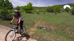 Girl mountainbiker cycling a single track exiting camera left Stock Footage