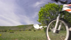 Girl mountainbiker cycling on a meadow near large satellite dishes Stock Footage