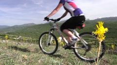 Girl mountainbiker cycling on a meadow, front flower in focus Stock Footage