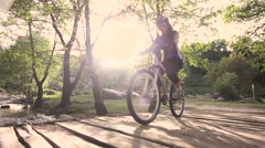 Girl mountainbiker cycling on a wooden bridge over a river. slider shot Stock Footage