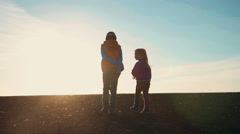 Boy and girl walking outside at sunset Stock Footage