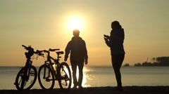 Romantic couple at sunset. Silhouette of bicycles on sunset Stock Footage