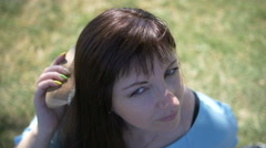 Young woman brushing her hair looking at the camera and smiling Stock Footage