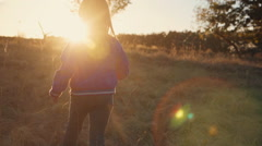 Young blonde girl running at sunset Stock Footage