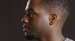 Portrait of a young black man in profile and then looking at camera Stock Footage