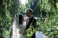 Beautiful wedding couple hugging in the park Stock Photos