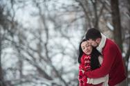 Man and woman hugging in snow-covered park Stock Photos