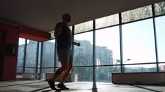 Man jump on skipping rope in gym Stock Footage