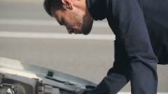 Man trying to repair a broken car Stock Footage