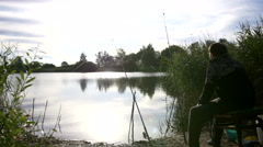 Fisherman sits and waits for fish on a fishing trip at dawn, fishing in the pond Stock Footage
