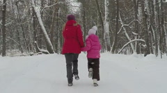 Mother with child hold hands and run in park at winter day. Slowmotion Stock Footage