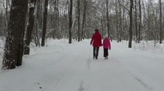 Mother with child hold hands and walk in park at winter day. Slowmotion Stock Footage