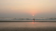 Woman relaxing on the Goa beach in sunset rays Stock Footage