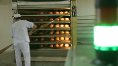 Just baked. Close-up of man taking the fresh baked bread out of oven Stock Footage