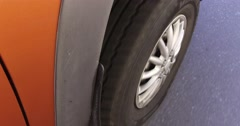 4K close up of car tire spinning as vehicle drives down the road Stock Footage