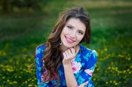 Portrait of young woman rest in the park smiling on the grass Stock Photos