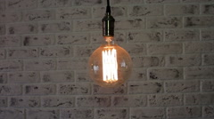 Vintage Loft lamp swinging on a brick wall background Stock Footage