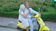 Mature couple sitting on scooter. Stock Footage