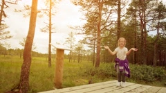 Little beautiful girl walks on swamp in Estonia Stock Footage