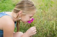Sweet blonde little girl on the meadow with purple flowers Stock Photos