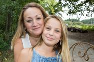 Mother and daughter hugging in love playing in the park Stock Photos