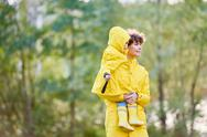 Mother walking with her daughter in raincoats Stock Photos