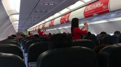 Stewardesses of the Air Asia company demonstrates how to use an oxygen mask Stock Footage