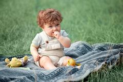 The little baby or year-old child on the grass in sunny summer day Stock Photos