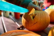 Close-up of man carves details of a jack o' lantern on Halloween Stock Photos