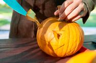 Close up of man's hand cutting with knife a pumpkin as he prepares a jack-o-lant Stock Photos