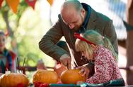 Father showing his daughter how to make Jack o'Lantern Stock Photos