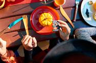 Close-up of people sitting at the table and eating cookies on Halloween party Stock Photos