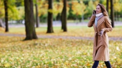 Woman with smartphone walking in autumn park Stock Footage