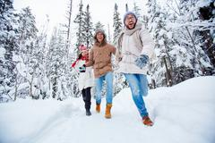 Happy friends running in winter forest Stock Photos