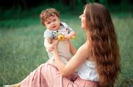 Young beautiful mother sitting with her little son against green grass. Happy Stock Photos