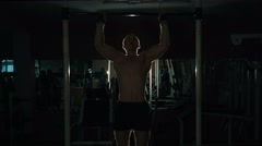 Man exercising cross training arms on workout bar gym , lowlight Stock Footage