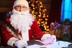 Santa Claus sitting at the table and writing letters Stock Photos