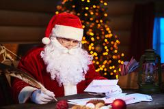 Santa Claus sitting at home and writing on paper to do list with quill pen Stock Photos