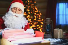 Santa Claus in eyeglasses working with letters from children Stock Photos