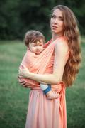 Young beautiful mother hugging her little toddler son against green grass. Happy Stock Photos