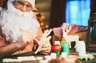 Smiling Santa decorating toys for Christmas Stock Photos