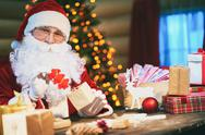 Santa Claus sitting at the table and preparing gifts for holidays Stock Photos