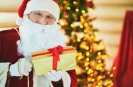 Santa Claus holding gift box Stock Photos
