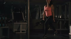Girl workout at gym, doing lunge with barbell , lowlight Stock Footage
