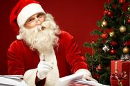 Santa Claus reading letters and looking at camera Stock Photos