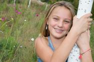 Sweet, happy and smiling young girl in a park Stock Photos